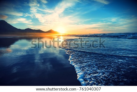 Beach sunset with endless horizon and lonely figures in the distance, and incredible foamy waves. Volcanic hills in the background #761040307