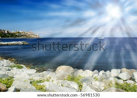 Beach surrounded by rocks with a blue sky. Panorama