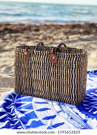 Beach towel and beach tote on the beach sand and the beach background