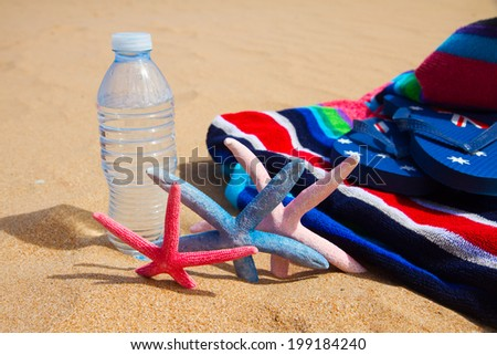 beach towel and bottle of cool water on sandy beach