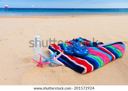beach towel and bottle of cool water on sandy beach by sea side