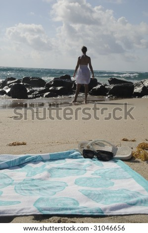 Beach towel and sunglasses, with woman in sand off in the distance