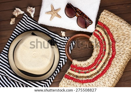 Beach towel, sunglasses and straw hat on wooden background. Concept of vacation, relaxation