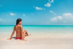 Beach travel Caribbean south vacation. Asian bikini woman relaxing sunbathing in water tanning enjoying sun. Winter holidays.