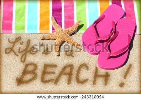 Beach travel fun sign. LIFE IS A BEACH written in sand with water next to beach towel, summer sandals and starfish. Summer and sun vacation holidays concept background.