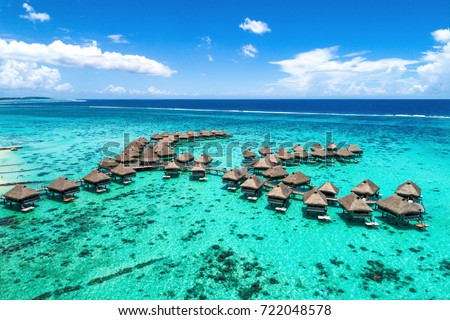 Beach travel vacation Tahiti hotel overwater bungalows luxury resort in coral reef lagoon ocean. Moorea, French Polynesia, Tahiti, South Pacific Ocean.