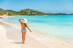 Beach travel vacation woman walking on luxury Caribbean cruise destination Antigua island in bikini wearing beach hat, carefree on holidays on Jolly Beach. Girl on travel vacation holidays swim model.
