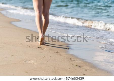 Beach travel - woman walking #574653439