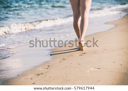 Beach travel - woman walking #579617944