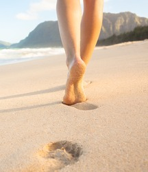 Beach travel - Woman walking on sand beach in Hawaii leaving footprints in the sand.