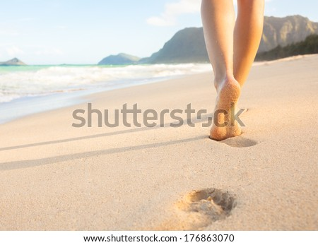 Beach travel - woman walking on sand beach leaving footprints in the sand. Closeup detail of female feet and golden sand on beach in Hawaii.