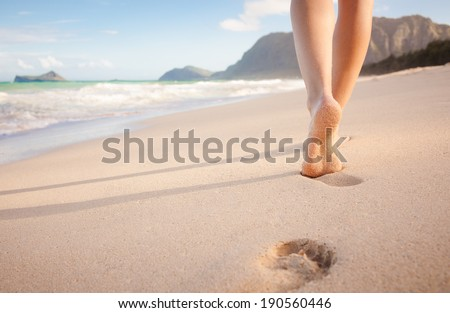 Beach travel - young girl walking on sandy beach leaving footprints in the sand, Hawaii, USA.