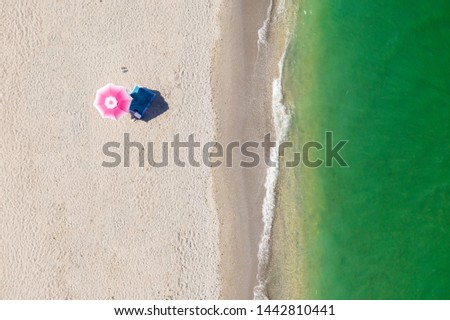 Beach umbrella alone on the seashore. Top view. Aerial View. Golden sand and green ocean waves. Bird eye view on the beach. Umbrella, waves, green ocean and relaxing vibes. Exotic exotic holiday