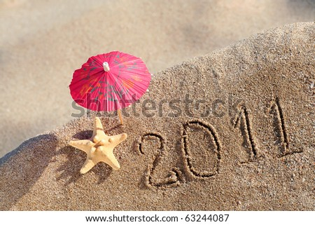 Beach Umbrella standing in the Sand with a Sea  Star near. New year 2011 at the beach!
