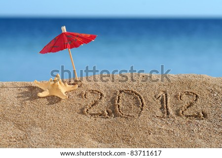 Beach Umbrella standing in the Sand with a Starfish near. New year 2012 at the beach!