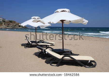 Beach umbrellas and beds facing about tides. Bulgaria, Black Sea.