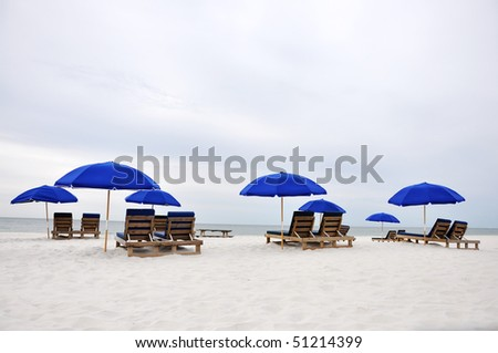 Beach umbrellas and chairs on deserted beach.