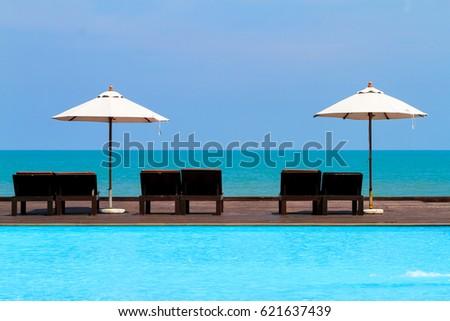 beach umbrellas and sunbathe seats near the sea, Thailand. #621637439