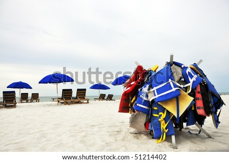 Beach umbrellas, chairs, and life jackets on deserted beach.