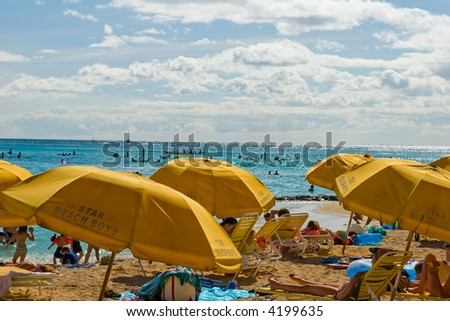 Beach umbrellas lining the ocean shore with people sun bathing