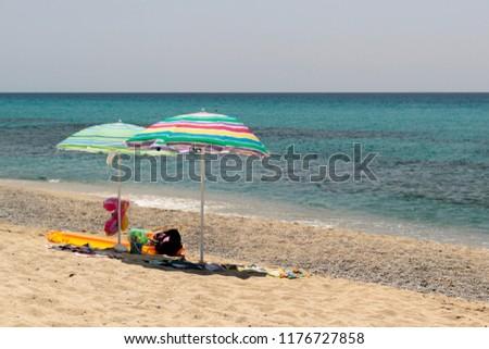 Beach umbrellas on the beach with white sand and the Tyrrhenian sea behind. Ricadi, Italy. #1176727858