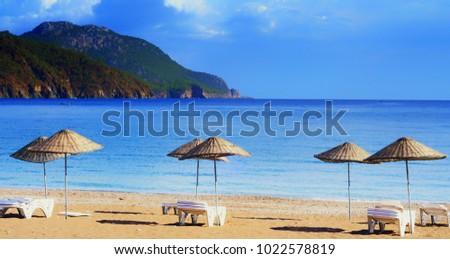 Beach umbrellas on the shore of the cozy bay of Adrasan, near Antalya and Kemer, which is in Turkey on the Mediterranean coast. October of 2017. Stok fotoğraf ©