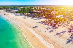 Beach vacation and travel background. Aerial drone view of beautiful atlantic tropical beach with straw umbrellas, palms and boats. Bavaro beach, Punta Cana, Dominican Republic