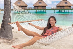 Beach vacation cheerful young Asian woman relaxing having fun in hammock by tropical luxury overwater bungalow resort.