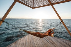Beach vacation cheerful young caucasian woman relaxing having fun in hammock by tropical luxury overwater bungalow resort.