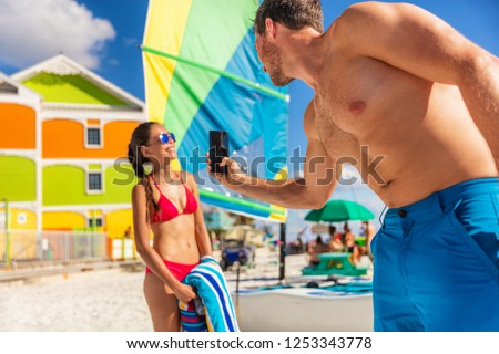 Beach vacation couple taking phone pictures - man taking pictures of model woman posing in bikini sun bathing in summer. Florida travel.