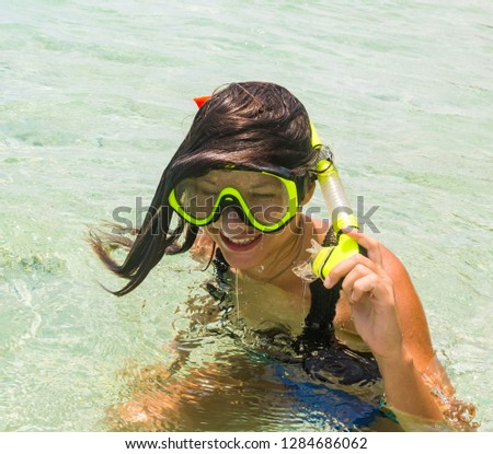 Beach vacation fun woman wearing a snorkel scuba mask making a goofy face while swimming in ocean water. Closeup portrait of Asian girl on her travel holidays. Summer or winter destination. #1284686062