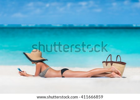 Beach vacation girl using mobile phone app texting sms or sharing photos on social media during summer travel holiday. Bikini woman relaxing sunbathing on sand lying on towel wearing sun hat.