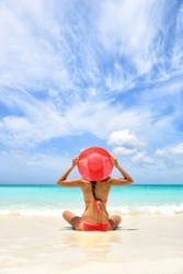 Beach vacation luxury travel cute fashion woman wearing pink swimwear and sun hat relaxing tanning in tropical destination. Girl tourist on summer holiday at vacation resort.