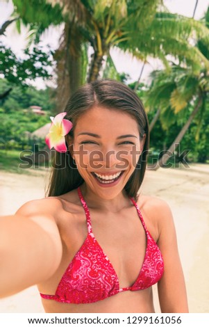 Beach vacation selfie bikini girl taking photo with phone camera. Smiling Asian woman taking holiday memories with smartphone app for self-portrait pictures. Tropical summer destination.