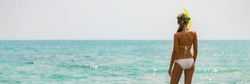 Beach vacation snorkel bikini woman going swimming in ocean with snorkeling mask on Caribbean holiday banner panorama. Summer vacation lifestyle.