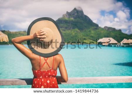 Beach vacation travel getaway summer holiday woman looking at view of Mt Otemanu on Bora Bora luxury hotel on romantic honeymoon. Tourist holding hat from behind enjoying Tahiti, French Polynesia. #1419844736
