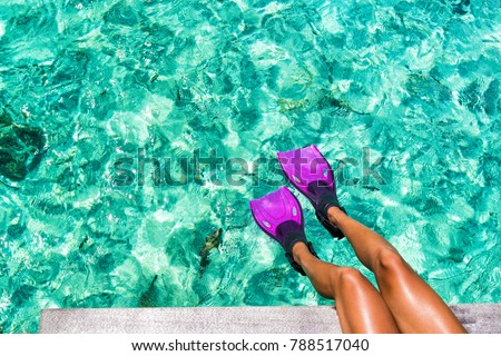 Beach vacation travel snorkel woman legs swimming in turquoise blue ocean tropical holiday texture background with fish in the sea. Swim fun in luxury resort destination.