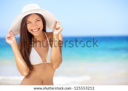 Beach vacation woman in sun smiling happy on summer holidays on tropical beach. Beautiful multiethnic asian chinese / caucasian bikini model wearing beach hat.