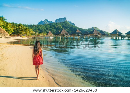 Beach vacation woman walking on Bora Bora island in Tahiti, French Polynesia at sunset with Mount Otemanu and overwater bungalows luxury hotel in the background. #1426629458