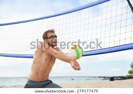 Beach volleyball man playing game hitting forearm pass volley ball during match on summer beach. Male model living healthy active lifestyle doing sport on beach.