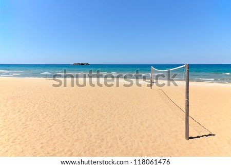 Beach Volleyball net on sandy beach with sea and blue sky in the background