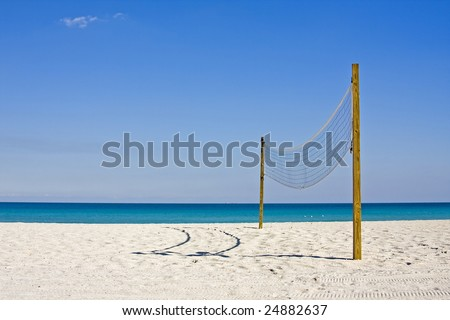 beach volleyball on a sunny summer day with blue sky and ocean background