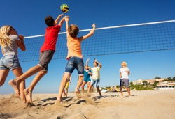 Beach volleyball players jumping to spike the ball