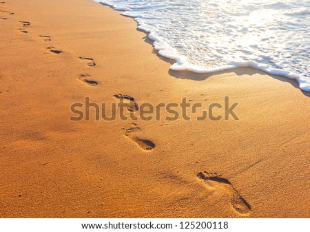 beach, wave and footsteps at sunset time