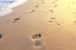 Beach, wave and footsteps in Greece, yellow sun