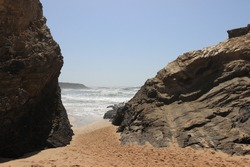 Beach way in between 2 big rocks with hectic waves