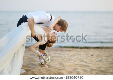 Beach wedding: bride and groom hugging by the sea