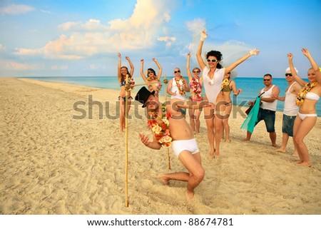 Beach wedding of happy newlywed couple have fun doing the limbo