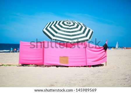Beach wind shelter and parasol on the beach