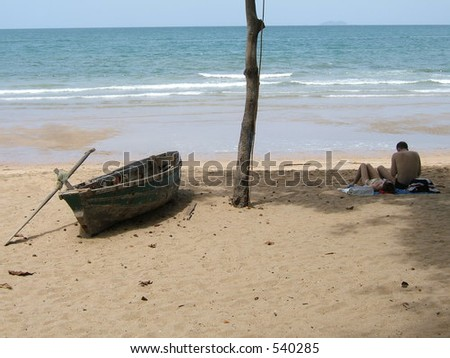 Beach with a boat and a couple